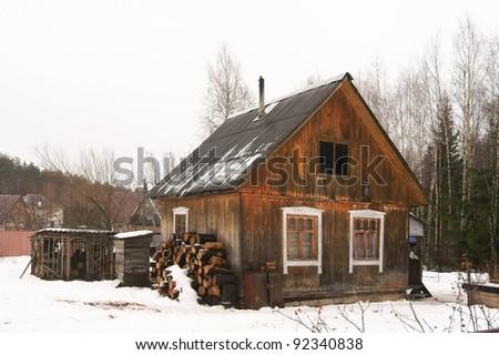 Rural poor house in winter - stock photo