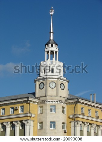 Russia, Voronezh. The big yellow building with a high spike on a roof and hours, against the dark blue sky, a sunny day - stock photo