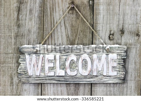 Rustic wood welcome sign with snow hanging on old antique wooden door - stock photo