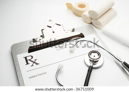 rx prescription on clipboard with stethoscope and bandages - stock photo