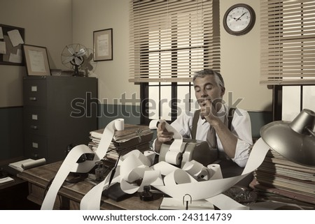 1950s accountant checking calculations in his office with hand on chin. - stock photo