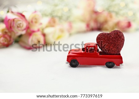1950's antique vintage red truck hauling a glittery red heart past a roll of beautiful long stem roses. Extreme shallow depth of field with selective focus on vehicle.