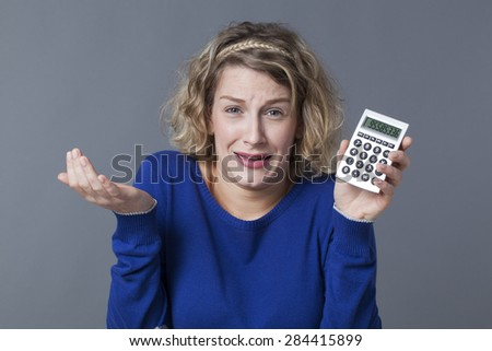 20s blonde girl scared of figures shown on her calculator - stock photo
