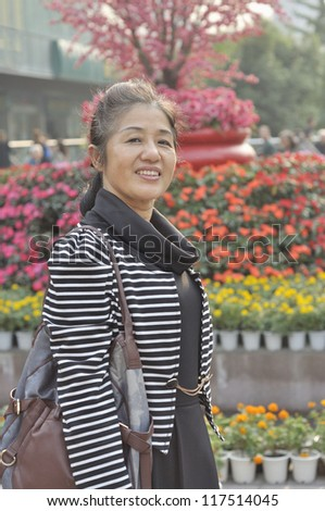50's chinese woman at park - stock photo