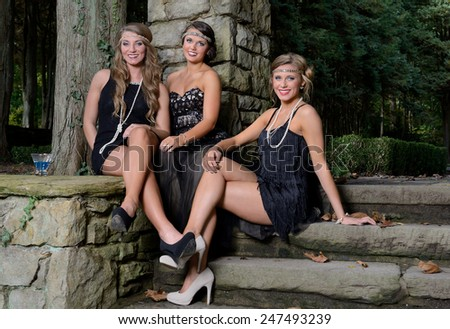 1920's fashion shoot - Three stunning young Caucasian women wearing black vintage appearing dresses with headband seated together in outdoor garden area at top of stairs - stock photo