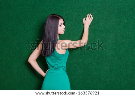 20s female weared green dress backside view. Cute lady against green wall from back