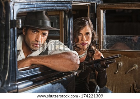 1920s gangster duo in car with shotgun on look out - stock photo