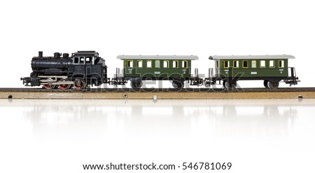 1950s model electric train formed by a steam locomotive and two passenger cars on the rails