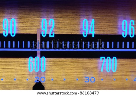 70 s Old radio dial close-up with glowing scale numbers - stock photo