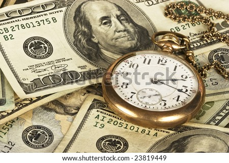 1800's railroad pocket watch sitting on a stack of U.S. cash reflecting time and money - stock photo