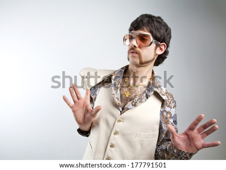1970s retro man in a white leisure suite and sunglasses looking surprised - stock photo