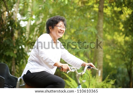 60s senior Asian woman riding on bicycle outdoor with great fun - stock photo