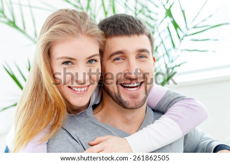 50s. Smiling woman hugging her husband on the couch from behind at home in the living room - stock photo