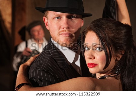 1920s style couple dancing with musician in background - stock photo