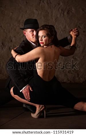 1920s style male tango dancer holding his dance partner - stock photo