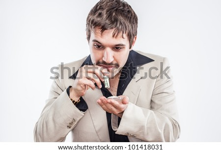 70's Vintage Mustache Cocaine Coke Head Drug addict. Man wearing leisure suit with black collar and tan jacket is snorting coke through rolled up dollar bill.  White background.