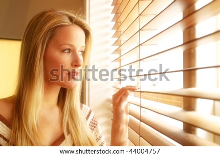 20s woman in her home looking out through her venison blinds in black and white