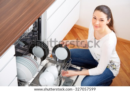 20s woman in kitchen, empty out the dishwasher, looking to the Camera - stock photo