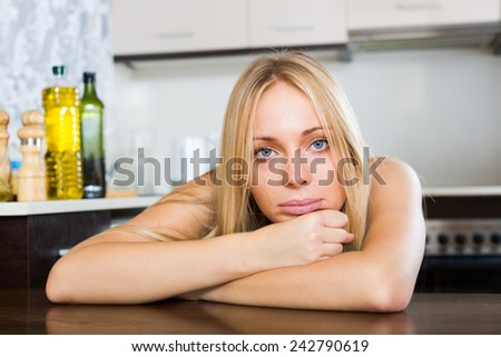 Sad  blonde  woman sitting   in kitchen - stock photo