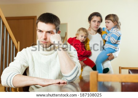 Sad family with two children having quarrel at home - stock photo