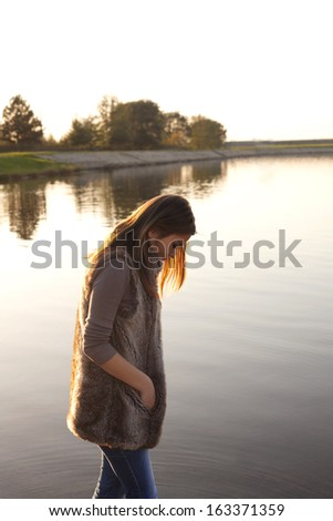 sad girl walking on the beach - stock photo