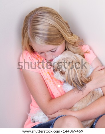 Sad teen in corner holding her shih tzu dog for comfort - stock photo