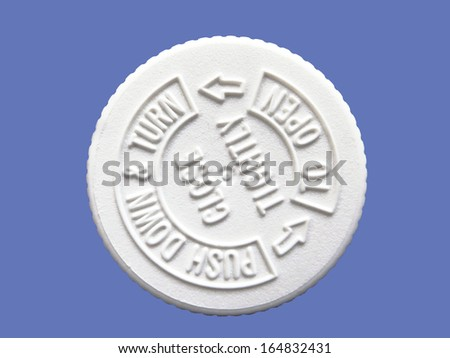 Safety cap for prescription pill container isolated on blue                          - stock photo