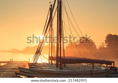 Sailing boats at a jetty during a tranquil, foggy sunrise. - stock photo