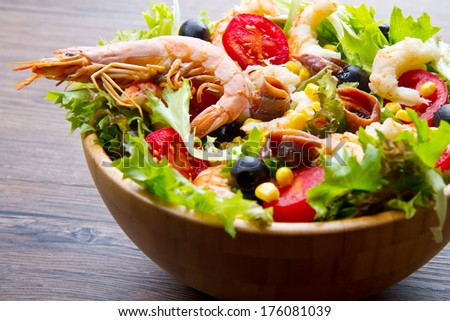salad of shrimp, mixed greens, black olives anchovies and tomatoes on wooden background - stock photo