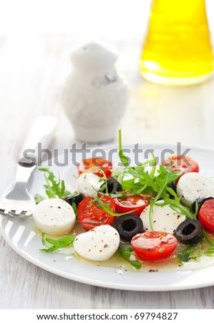 salad with mozzarella, tomatoes and black olive - stock photo