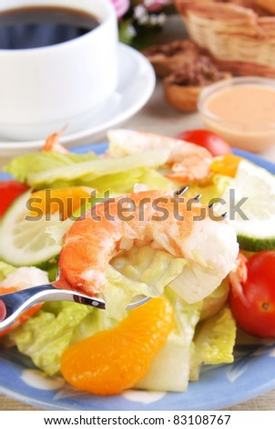 Salad with shrimp and tomatoes on a  plate