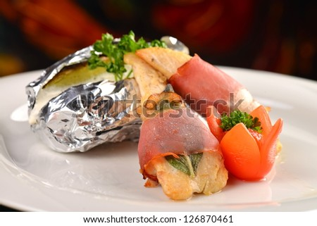 Saltimbocca - Italian speciality, veal chops with prosciutto and sage leaf, served with baked potato in alu foil - stock photo
