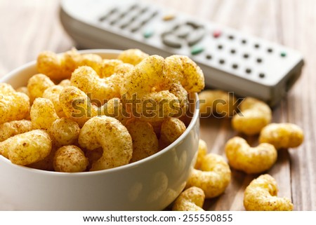 salty snacks with television - stock photo