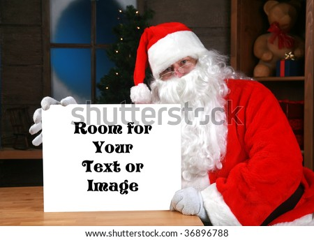"""santa claus"" holds a blank white sign with ""room for your text or image""  while in his workshop in the ""north pole"" - stock photo"