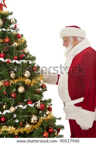 Santa Claus or father Christmas decorating  Christmas tree, side view, isolated on white background - stock photo