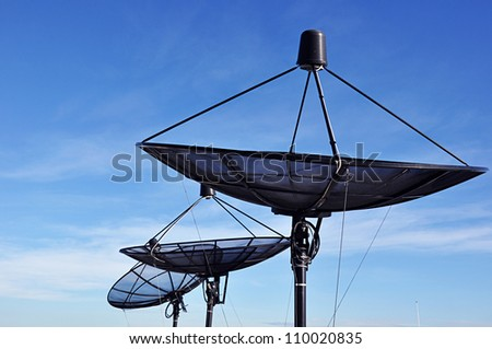 Satellite dishes against blue sky background