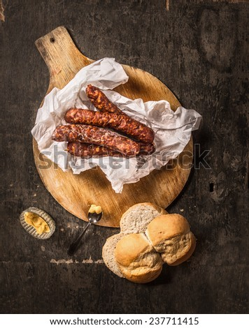 sausage on round cutting board with bread and mustard , dark wooden background, top view - stock photo