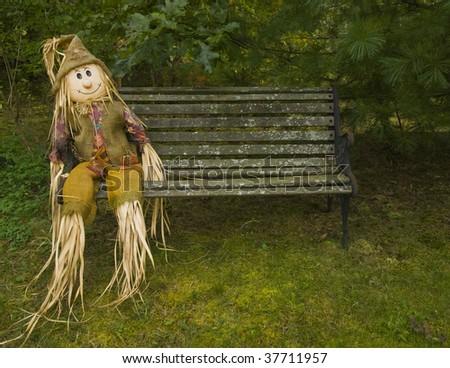 scarecrow on a park bench. - stock photo