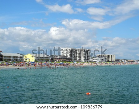 Scenic view of Old Orchard Beach in Maine, from the end of the pier, several hundred feet out over the ocean, on a sparkling, sunny summer day. - stock photo