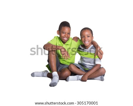 2 school aged brothers sitting on the floor looking at the camera with their arms around each other