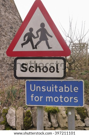 """""""School"""" and """"Unsuitable for Motors"""" Road Signs in the Rural Village of Parwich within The Peak District National Park, Derbyshire, England, UK - stock photo"""