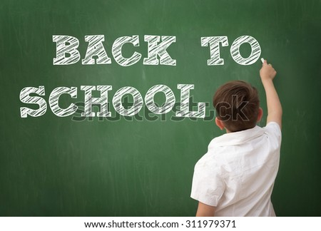 Schoolboy drawing BACK TO SCHOOL on blackboard, education concept - stock photo