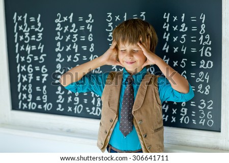 Schoolboy standing and writing something on chalkboard.  - stock photo