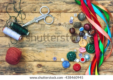scissors, thread, variety buttons,  multicolored ribbons lying on old wooden table - stock photo