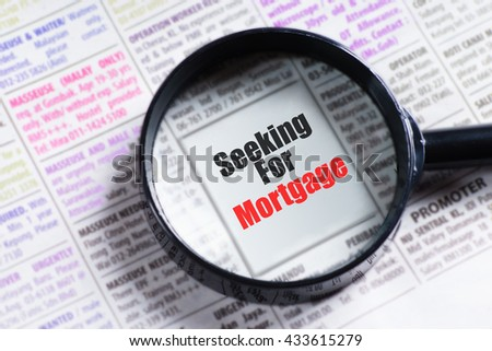 """Seeking For Mortagage"" red and black text on blurry image of newspaper with magnifying glass on it symbolic as search"