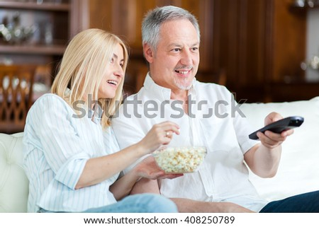 Senior couple sitting in couch and watching tv  - stock photo