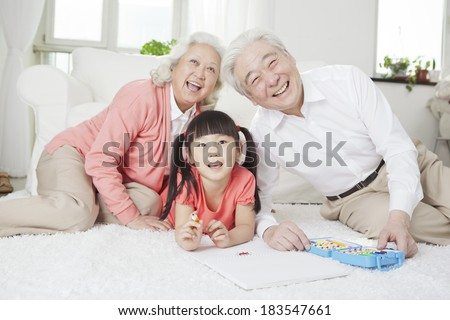Senior couple with granddaughter drawing