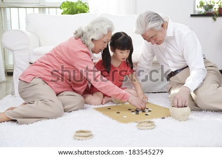 Senior couple with granddaughter playing game of go	 - stock photo