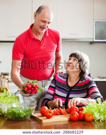 Senior man and mature woman  cooking vegetables lunch in home