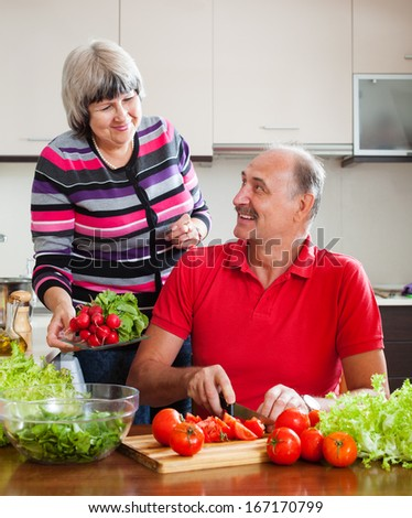 Senior man and mature woman  cooking vegetables lunch in home kitchen